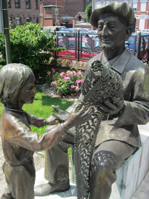 """Old tulliste and the child"". This is a statue of  Jules Bracq (1889-1990) that has been offered by his son Jean Bracq to the Lace Museum of Caudry.  Now you can find it near the front doors there."